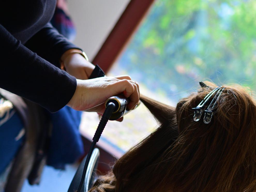 Imagen de una peluquera peinando a una clienta.