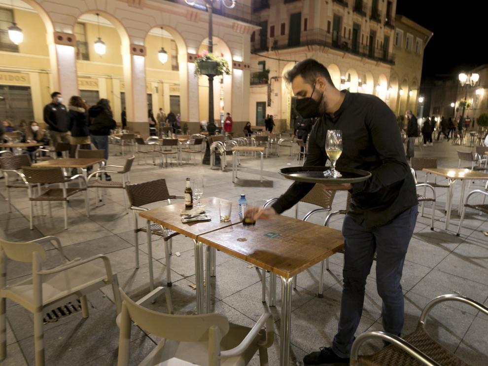 Un camarero limpia las últimas mesas para cerrar a las 20.00 en la plaza de López Allué de Huesca.