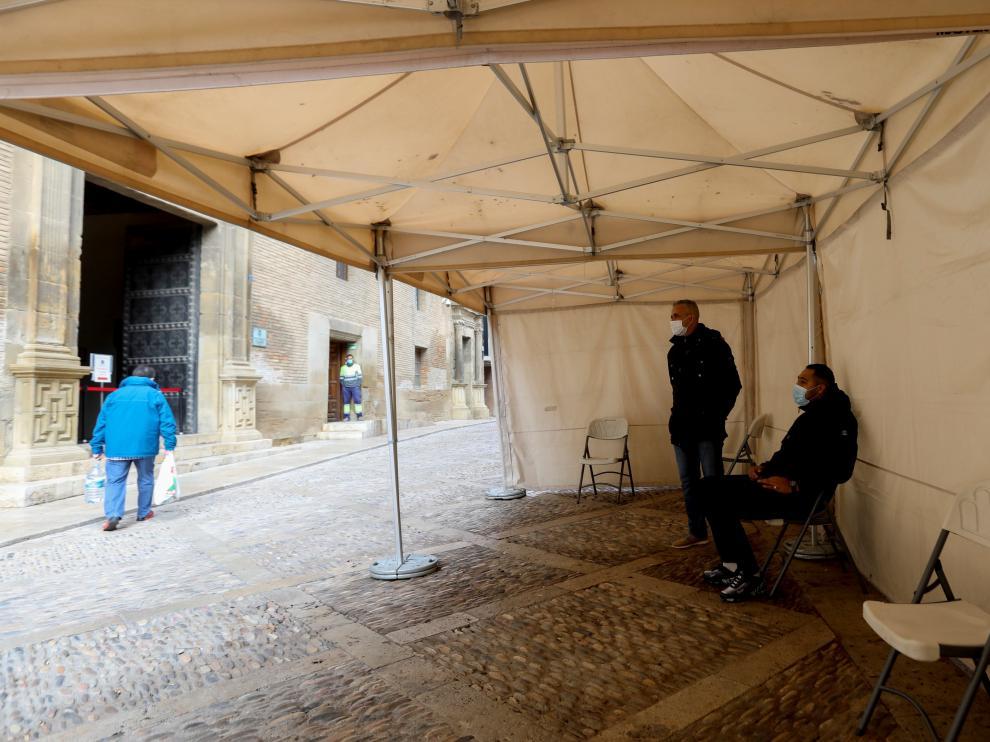 Dos personas aguardan bajo la carpa su turno en las oficinas municipales.