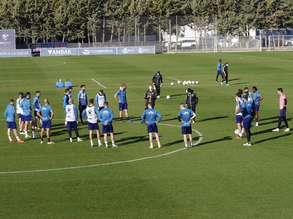 Los jugadores de la SD Huesca reciben instrucciones en el entrenamiento de este lunes.