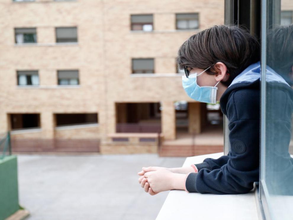 CREATOR: gd-jpeg v1.0 (using IJG JPEG v80), quality = 75Un niño se asoma a la ventana con mascarilla, en una población de Madrid.