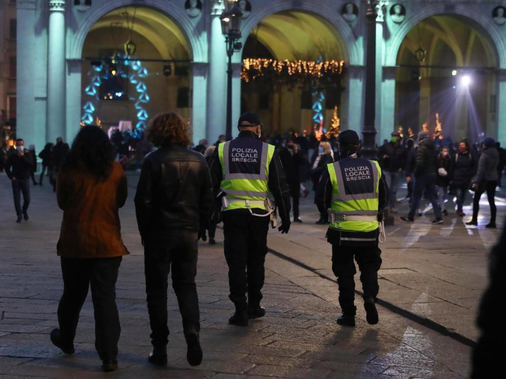 Dos policías patrullan por una calle de Brescia.
