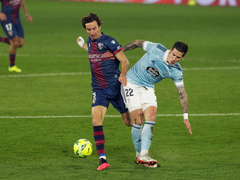 El jugador del Celta de Vigo Santi Mina , pugna por un balón, con el jugador del Huesca Mosquera