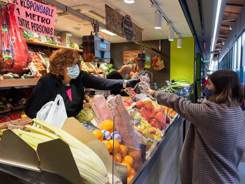 Una consumidora adquiere fruta en un puesto del Mercado Central de la capital aragonesa.