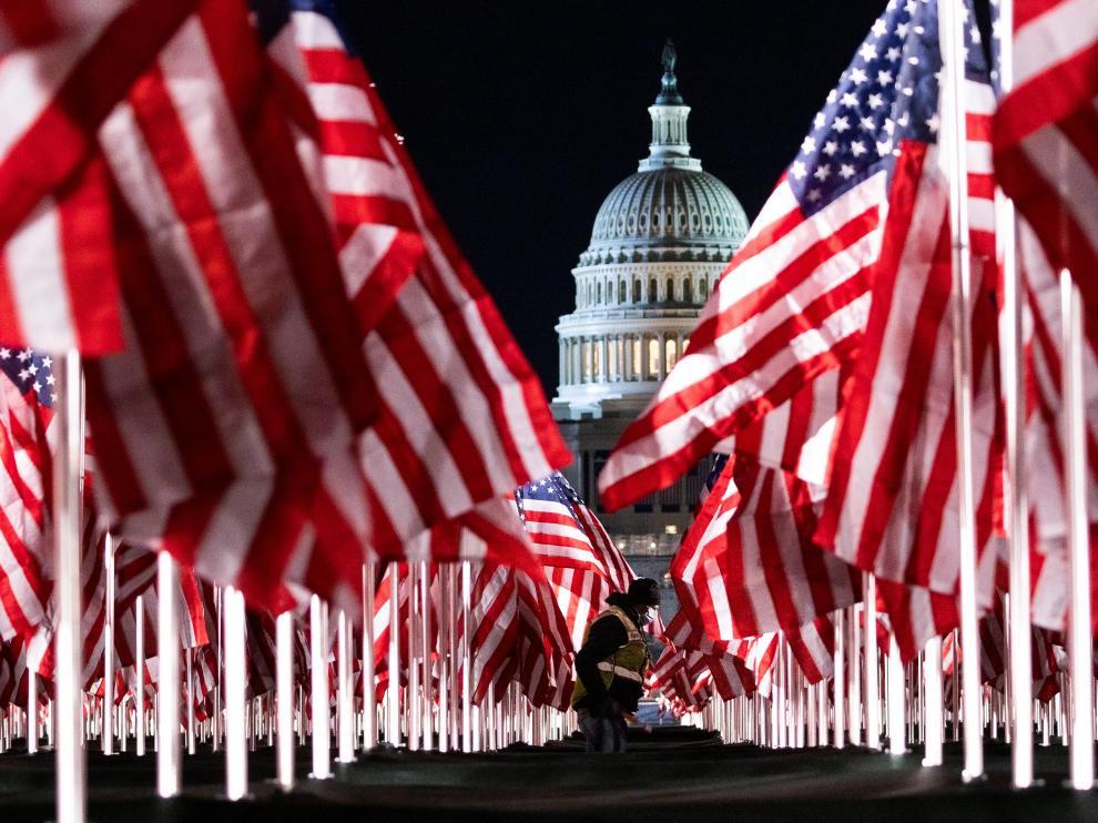 Una persona pasa entre las 200.000 banderas instaladas frente al Capitolio para la investidura de Biden.