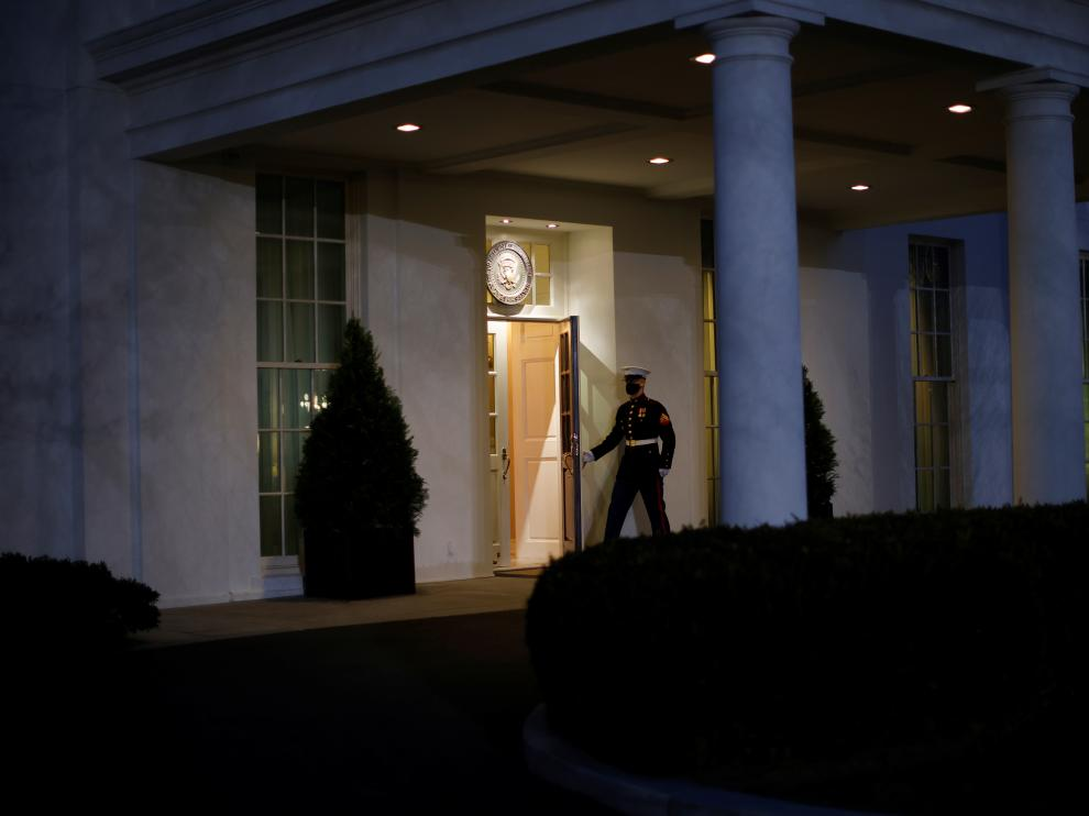 A U.S. Marine opens a door of the West Wing door, an indication that U.S. President Donald Trump is in the Oval Office during his last day in office, in Washington U.S.