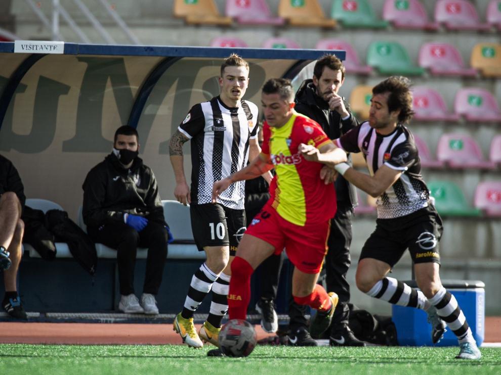 Carracedo conduce el balón ante la presión de un rival.