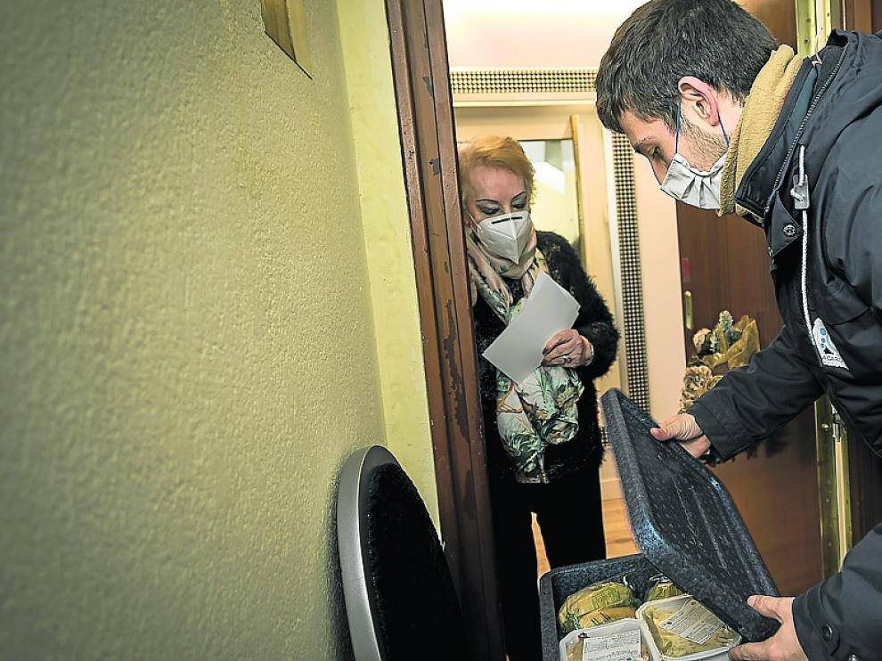 Mª Dolores Ruiz recoge el menú que le trae Javier Burguete.