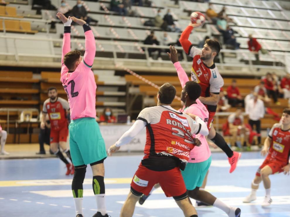 Joao Pinto intenta el lanzamiento ante la defensa del Barcelona.