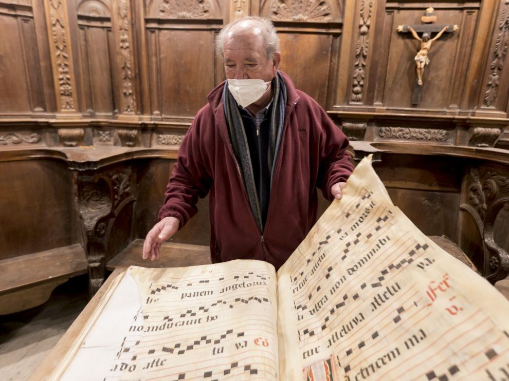 Aurelio Ricou, párroco de Roda, hojeando las páginas de unos antiguos códices de la catedral.