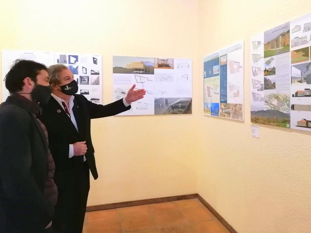 El alcalde de Aínsa, Enrique Pueyo, y el decano del Colegio de Arquitectos, Pedro J. Navarro observan los proyectos expuestos.