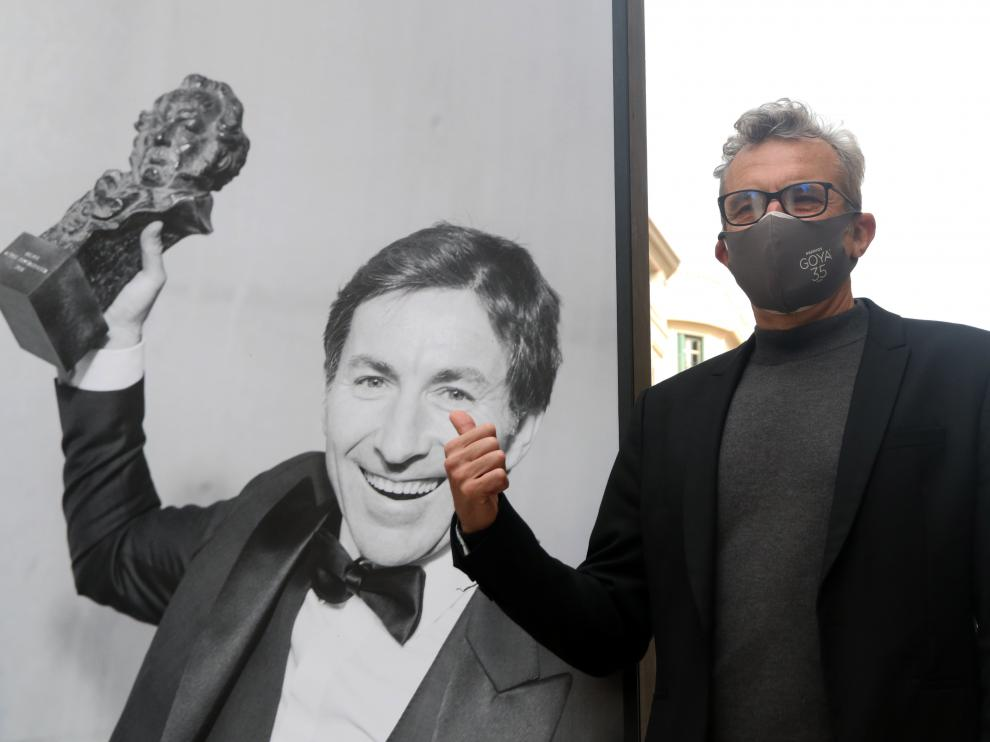El presidente de la Academia de Cine, Mariano Barroso, junto a una foto de una exposición en Málaga que celebra la gala de los Goya.