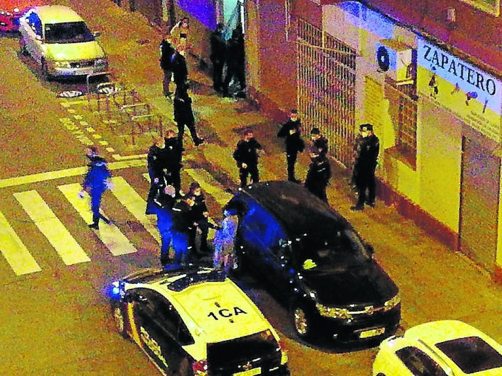 La detenida, entre el vehículo negro y un coche patrulla