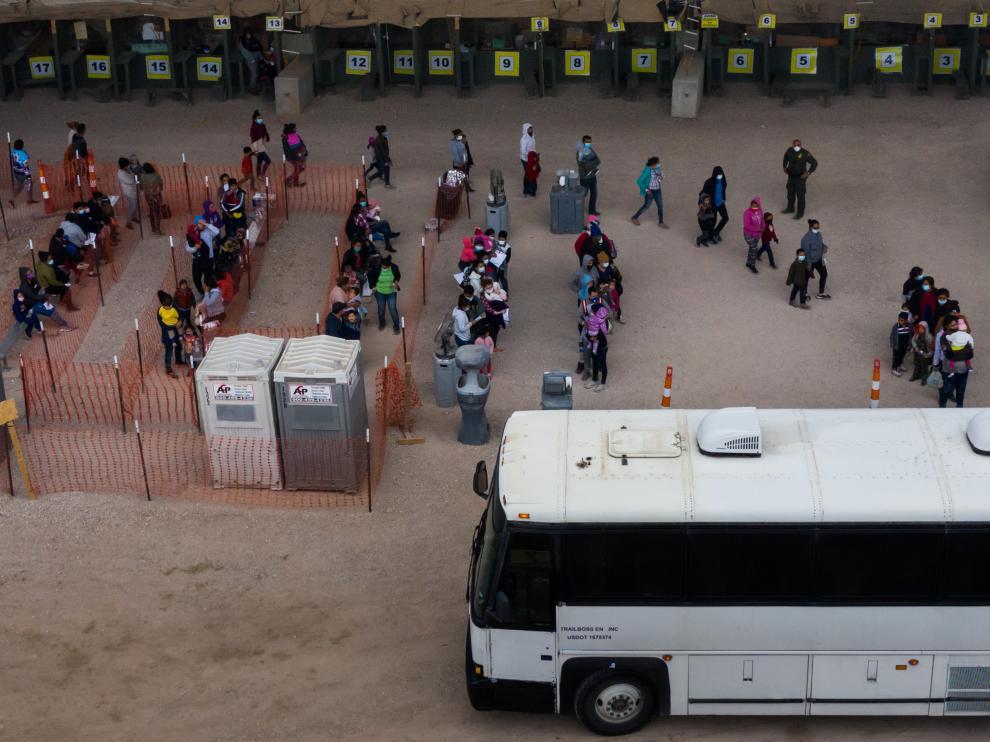 Decenas de solicitantes de asilo de Centroamérica esperan a ser llevados a un centro de procesamiento en Estados Unidos.