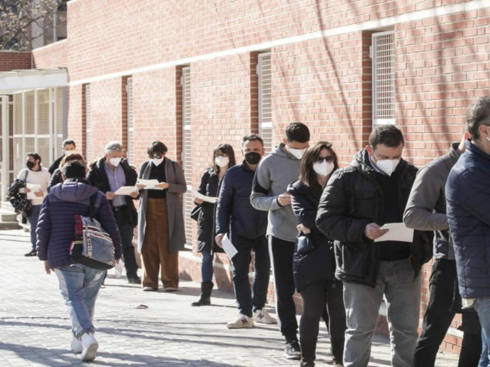 Fila de personas a la espera de ser llamados para vacunarse en el barrio de la Bombarda (Zaragoza).