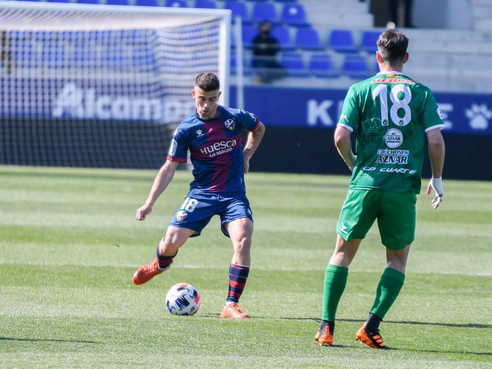 Carrasco, del Huesca, realiza un pase ante la presión de Andreu, del Cuarte.