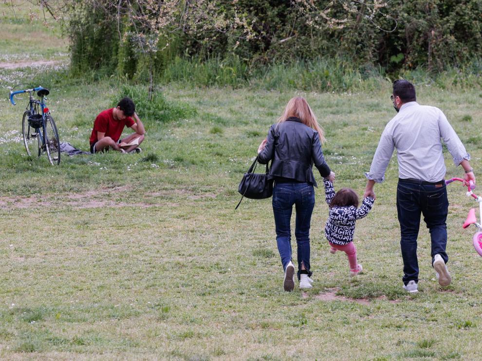 Unos padres pasean con su hija por un parque de Roma.