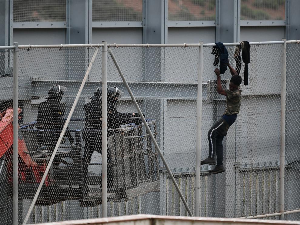 Un inmigrante intenta saltar la valla fronteriza de Ceuta, este martes.
