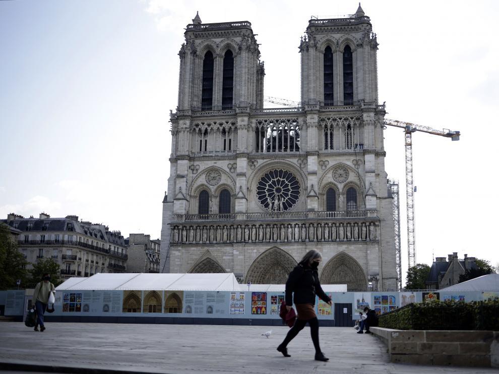 Una mujer pasa por delante de Notre Dame, la víspera de que se cumplan dos años del incendio.