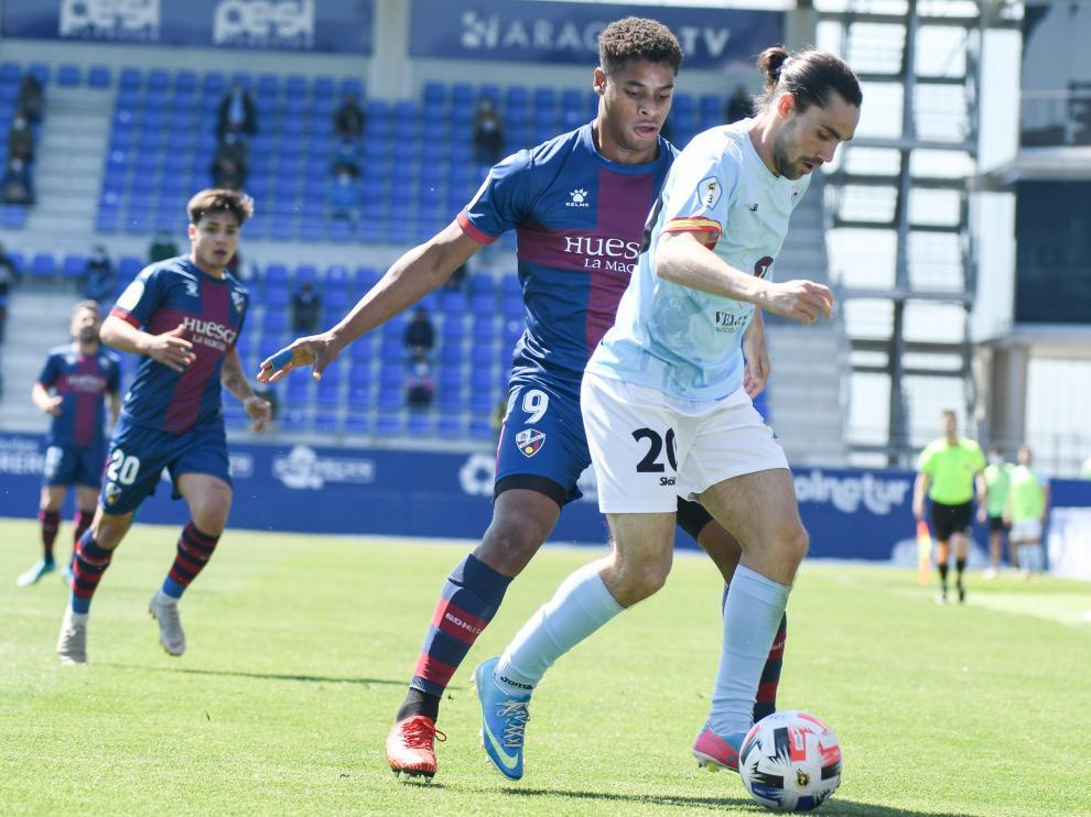 Barba, del Brea, protege el balón ante la presión de Carlos Kevin, del Huesca B.