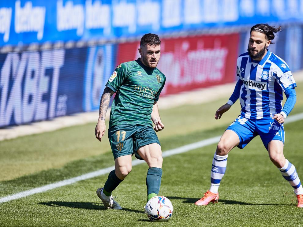Javi Galán, de la SD Huesca, conduce el balón frente a Jota, del Alavés.