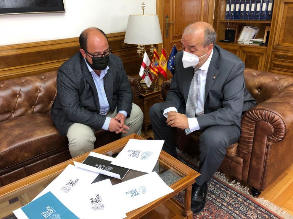 El presidente Rando y del vicepresidente Izquierdo, ante los distintos modelos del logotipo del Día de San Jorge de la DPT.
