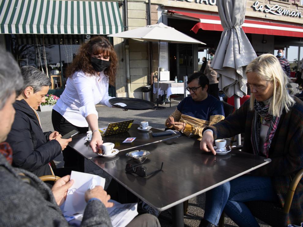 Un camarero con mascarilla sirve cafés a varios clientes en la terraza de un restaurante de Nyon. En Suiza los interiores de los bares siguen cerrados.