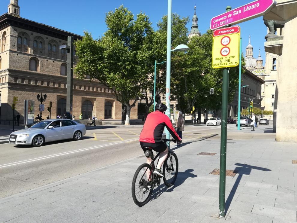 Un ciclista, este viernes, a su paso por la nueva señal que obliga a transitar a pie por el cruce del puente de Piedra.