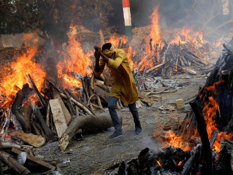 Un hombre pasa entre varias piras funerarias donde se crema a los muertos por covid.