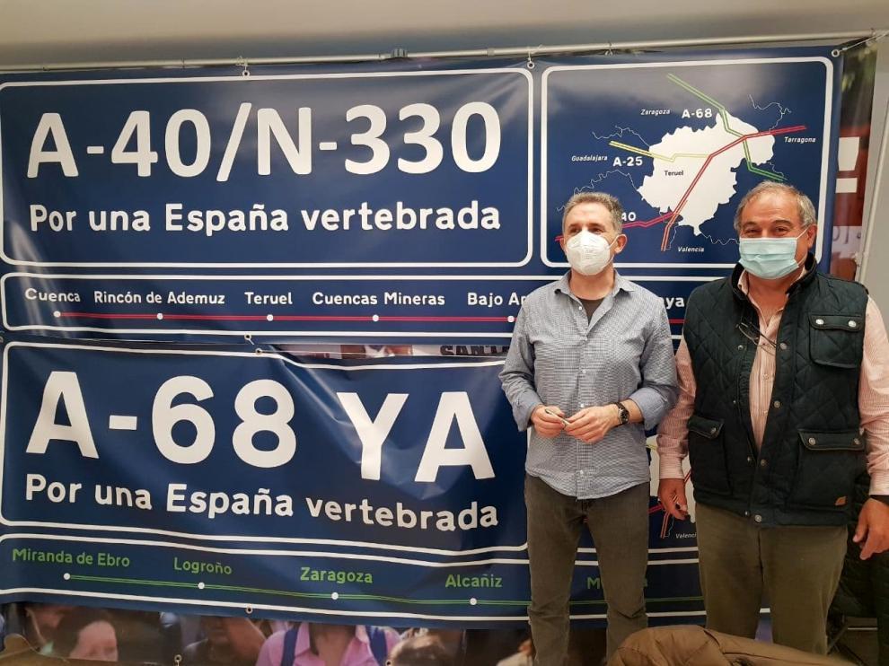 Dos colaboradores de Teruel Existe, Pascual Giménez -izquierda- y Enrique Marín, con las pancartas reivindicativas.