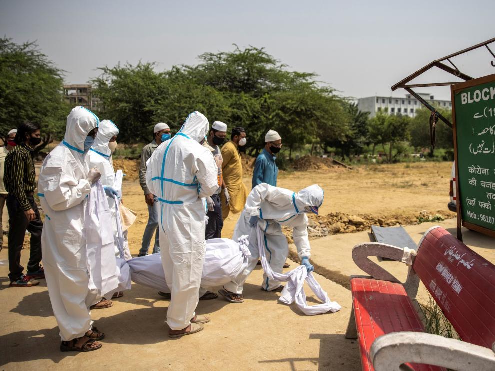 Trabajadores sanitarios retiran un cadáver de un enfermo de covid en India