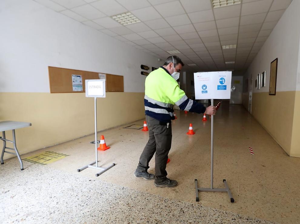 Un empleado de las brigadas municipales coloca los carteles de acceso a la sala de vacunación en el local vecinal.