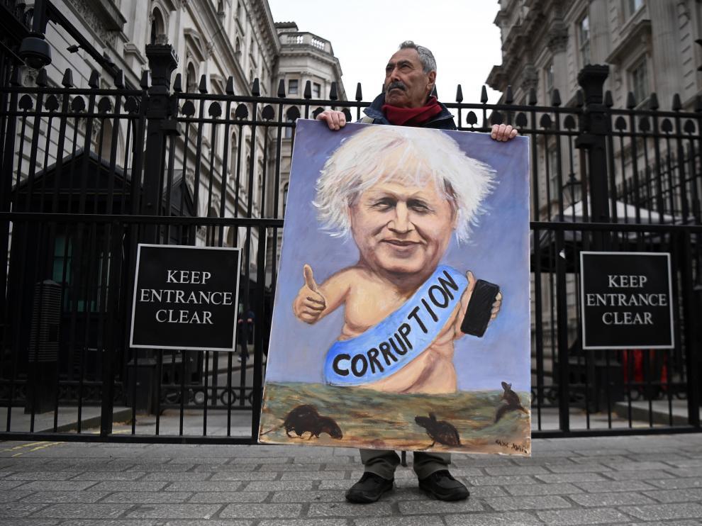 El dibujante satírico Kaya Mar, con una caricatura de Johnson delante de la residencia oficial del primer ministro