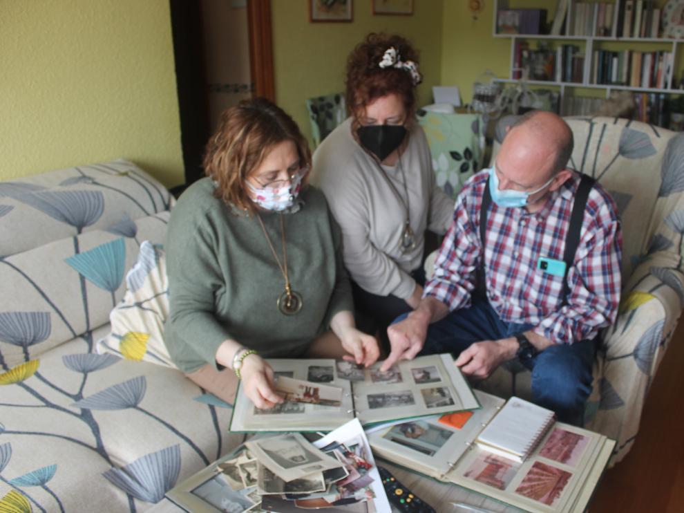 María Ángeles, Beatriz y Carlos hojean el álbum familiar, lleno de recuerdos de su madre, que murió durante el confinamiento, en abril de hace un año.