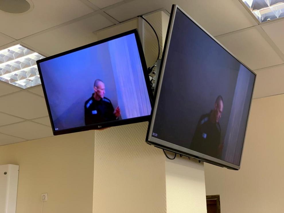 Navalni, en dos monitores de televisión durante su nueva vista judicial.