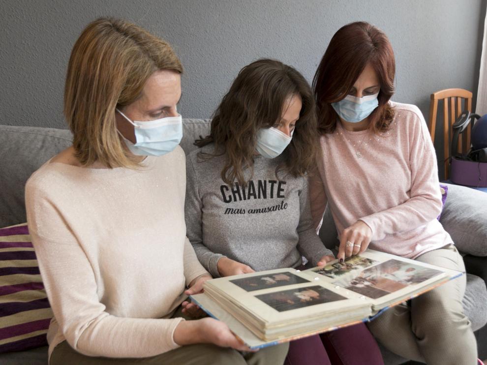 Las hijas de Andresa Bailo hojean un álbum familiar con fotos de su madre.