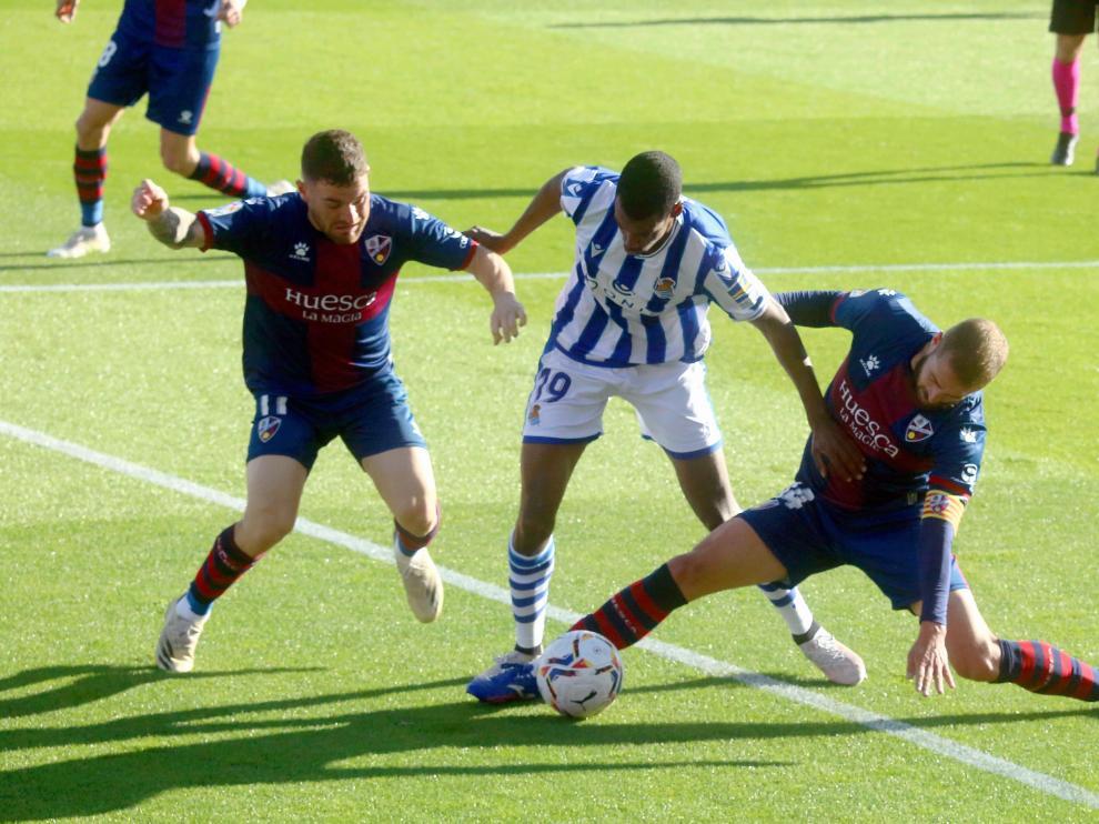 Pulido trata de cortar con Galán el avance de Isak durante el choque entre la SD Huesca y la Real Sociedad.