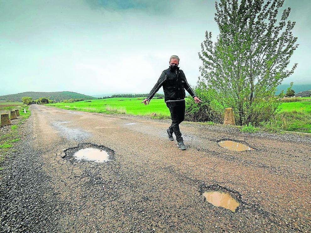 El alcalde de Luesma señala los baches que presenta la carretera A-1506.