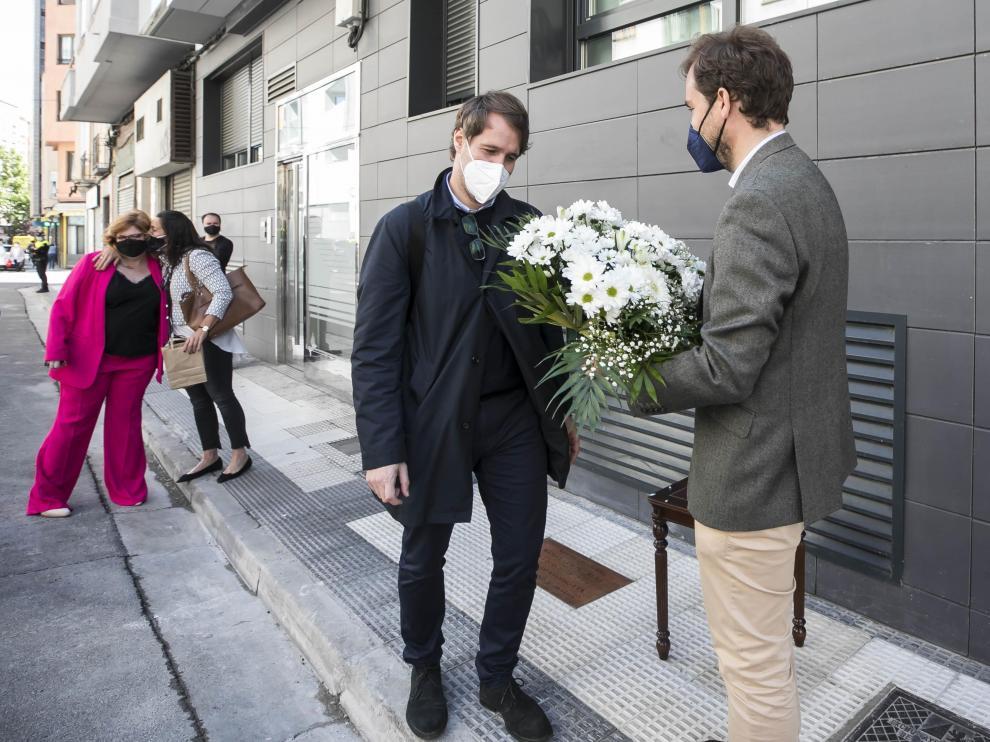 Borja Giménez, con un ramo de flores, y su hermano Manuel, ante la palca que recuerda el asesinato de su padre en la calle Cortes de Aragón el 6 de mayo de 2001.