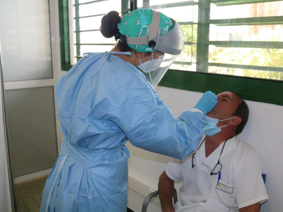 Una enfermera realiza una PCR a un sanitario en Canarias.