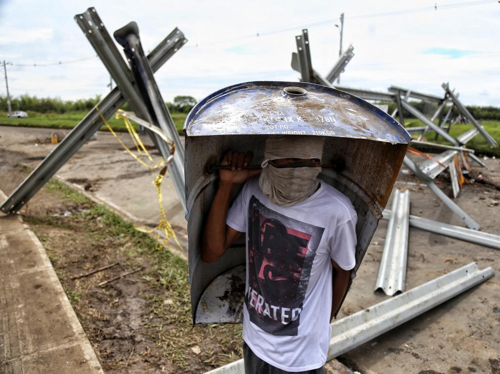Un joven se protege en la calle ante los disturbios