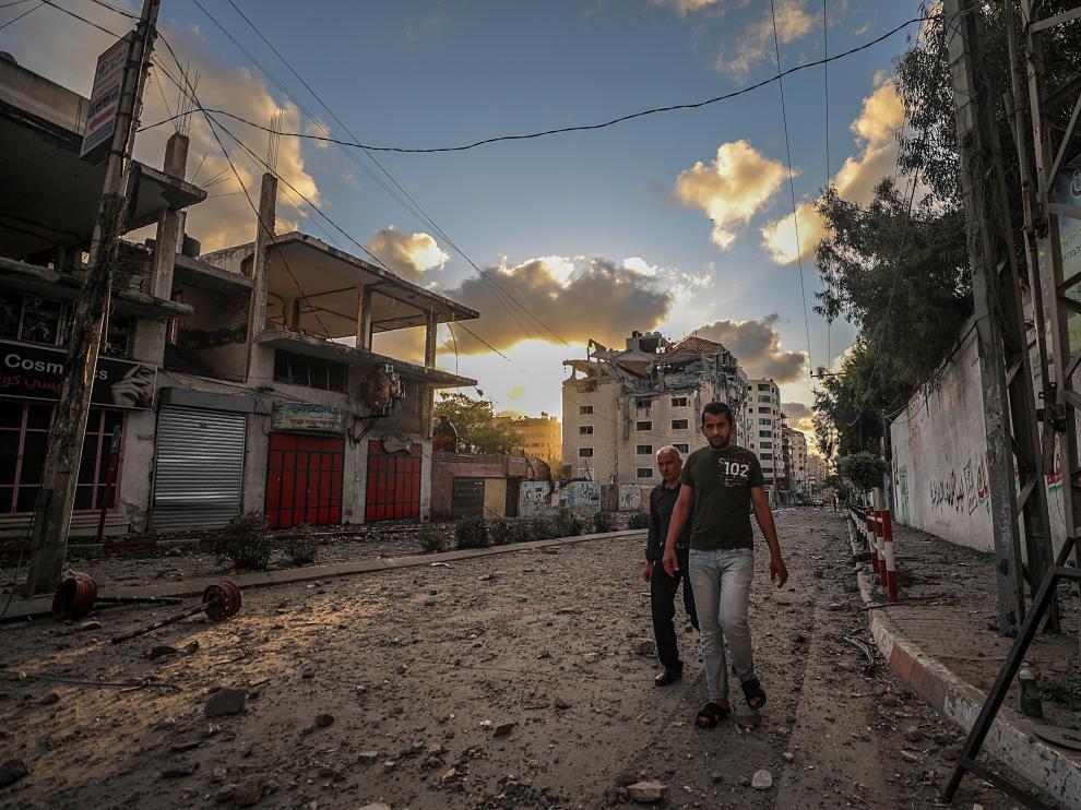 Dos palestinos caminan por una calle de Gaza, destrozada por los bombardeos israelíes