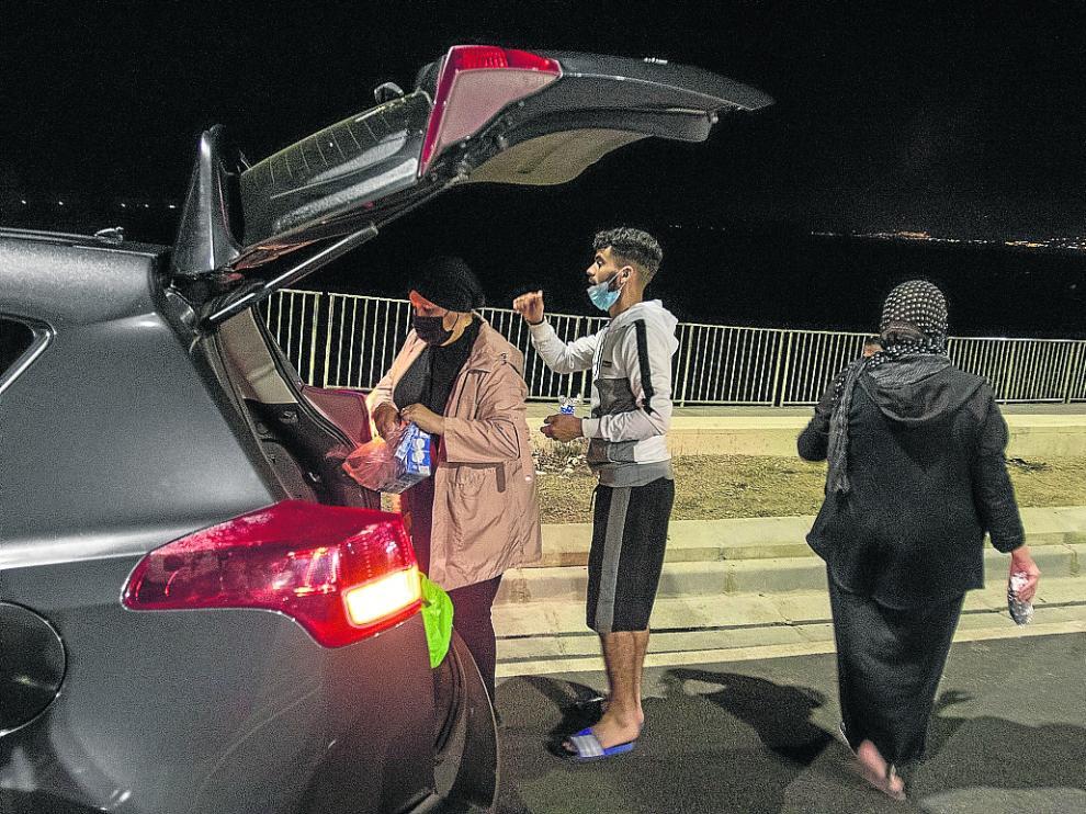 Sabah reparte ayer comida por las calles de Ceuta junto a su amiga Nayat y el joven Abdlghani.