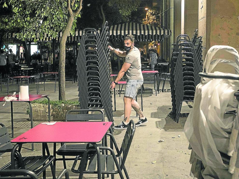 Un camarero recoge una terraza de bar en la plaza de San Francisco de Zaragoza.