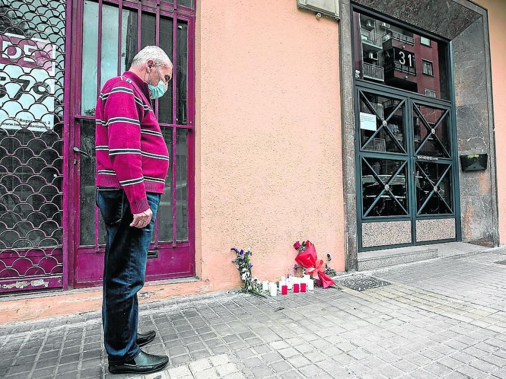 Un vecino del bloque, emocionado, observa las flores y velas depositadas en recuerdo de Katia.