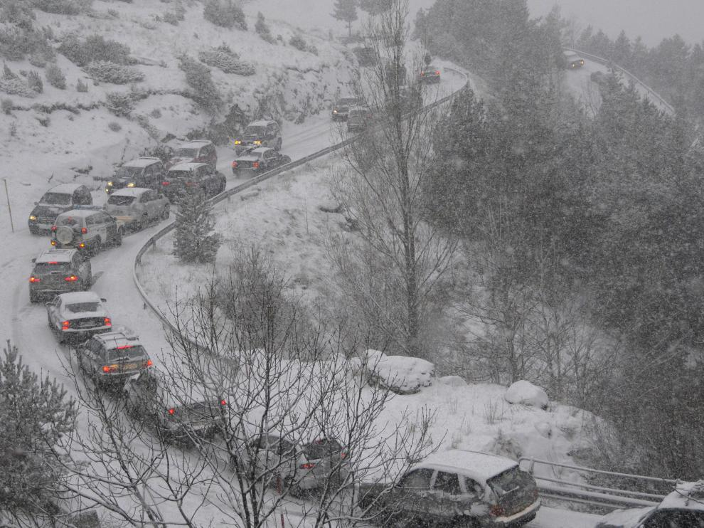 Colas de vehículos en la carretera que sube a la estación de Cerler en invierno.