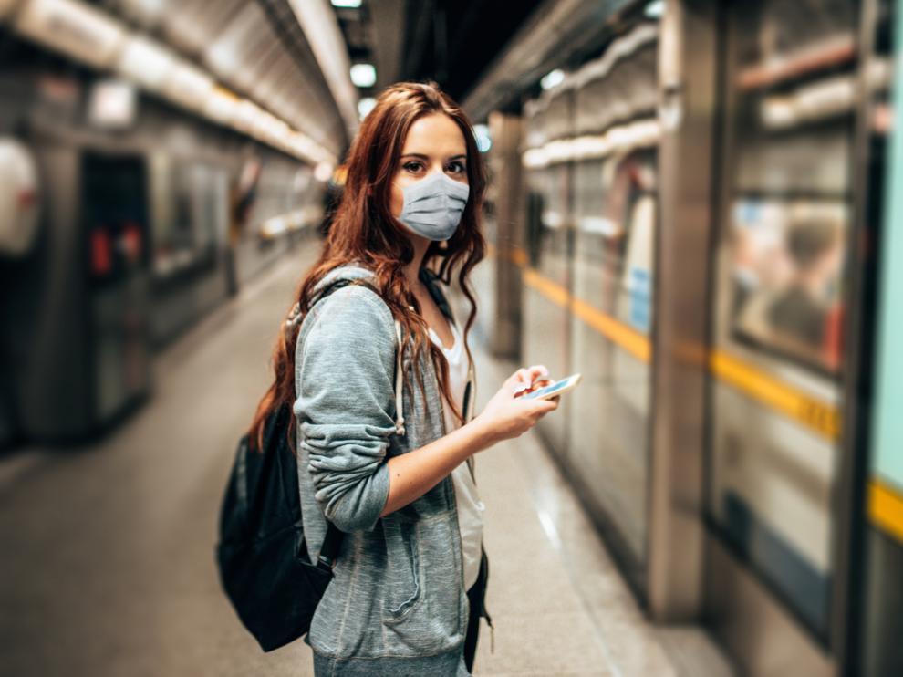 Mujer con mascarilla en la estación