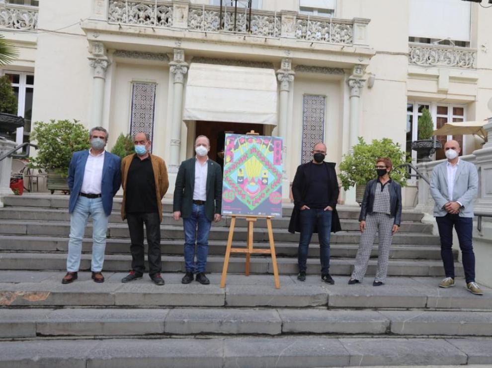 Representantes de las entidades que organizan y patrocinan el Festival de Cine de Huesca en la escalera del Casino junto al cartel de la edición de 2021