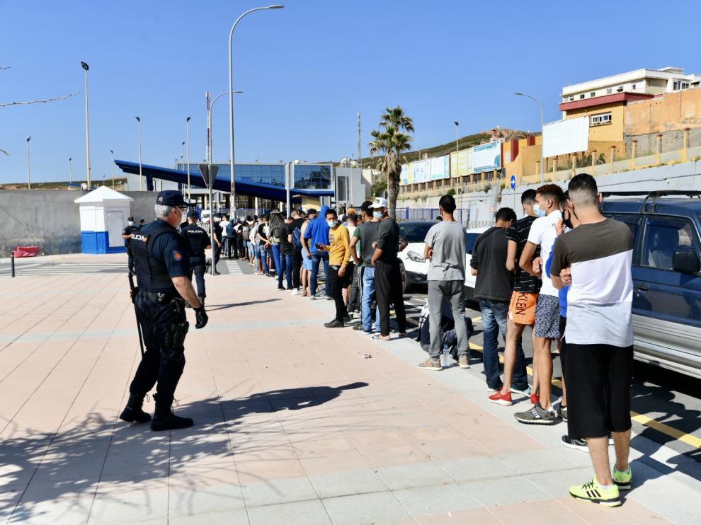 Varios migrantes procedentes de Marruecos hacen cola en las puertas de la frontera de Ceuta donde agentes de la Policía Nacional reparten citas para solicitud de asilo.