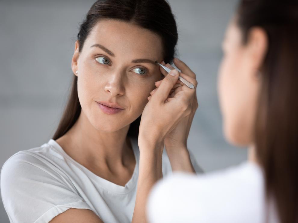 Una mujer retoca sus cejas con pinzas para un estilismo perfecto